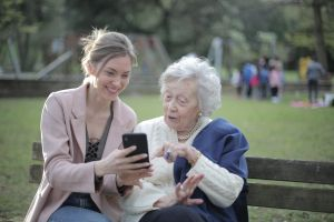 Photograph of Elderly woman with carer looking at phone