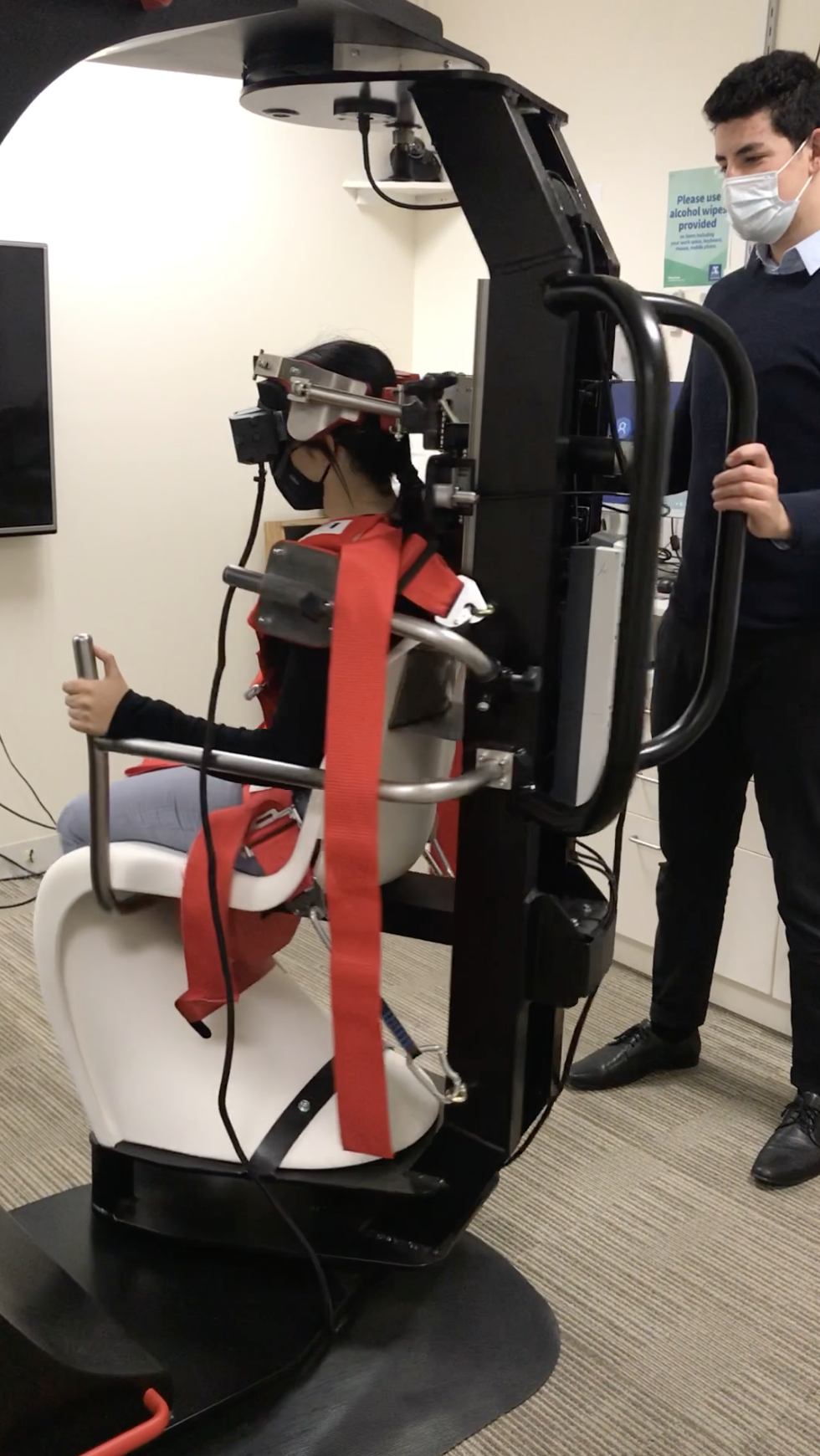 Patient using omnidirectional chair used to diagnose balance issues.