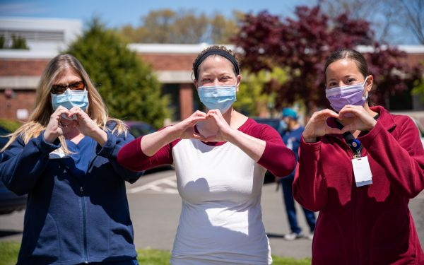 Three allied health workers at a hospital holding their hands in love heart shape while wearing masks