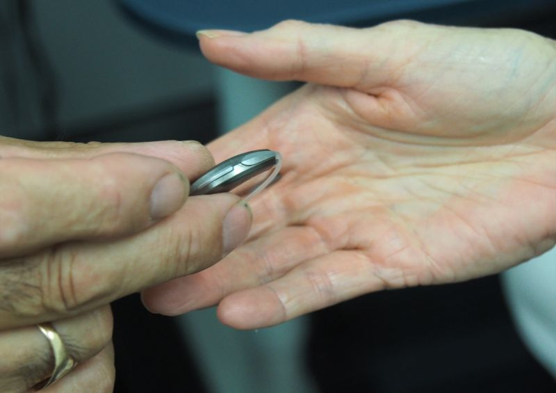 A hearing aid is being placed into someone's hand