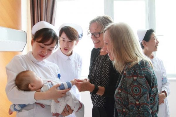 Professor Denise Harrison interacting with a baby in a Shanghai hospital