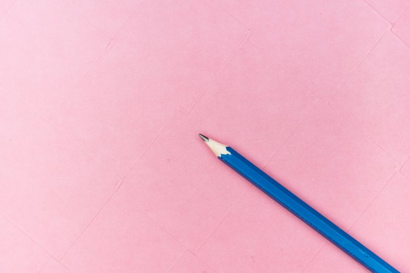 Blue pencil on a pink background