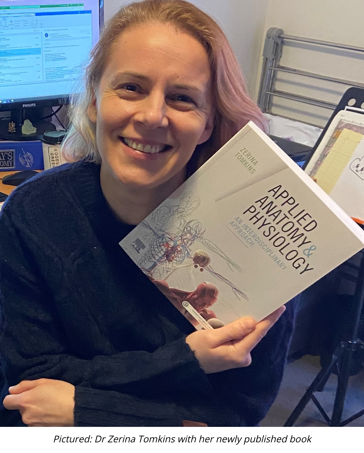 Dr Zerina Tompkins holding her newly published book