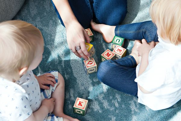 Photograph of toddlers with letter blocks