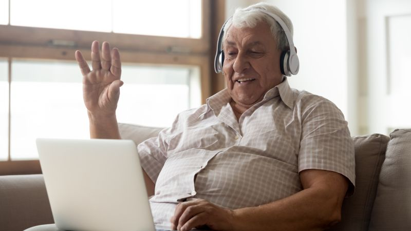 Man sitting on couch wearing headphones waves to a laptop
